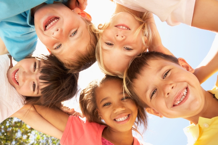 Young smiling children in a circle looking down